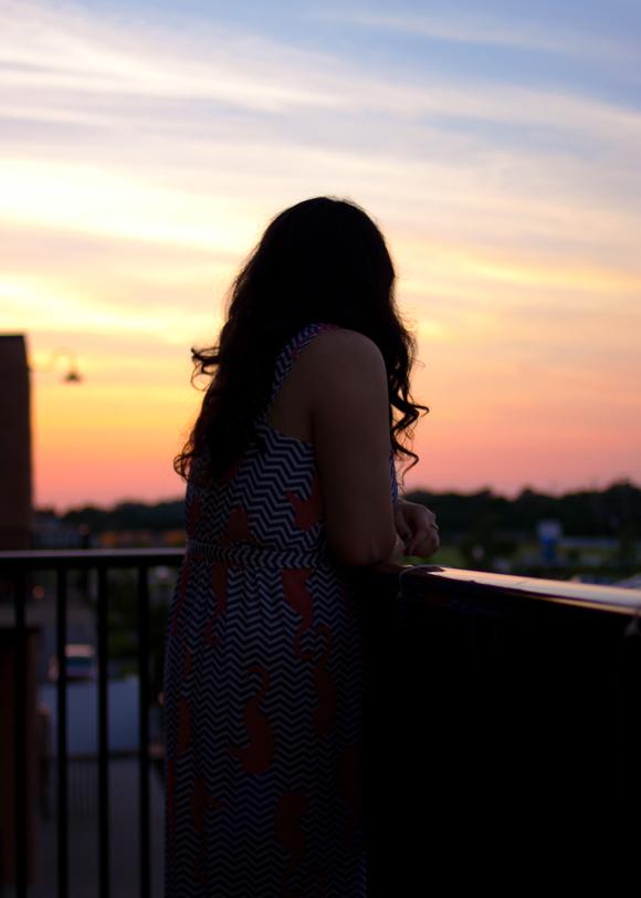 fashion blogger wearing tracy negoshian rihanna maxi dress on a balcony at sunset